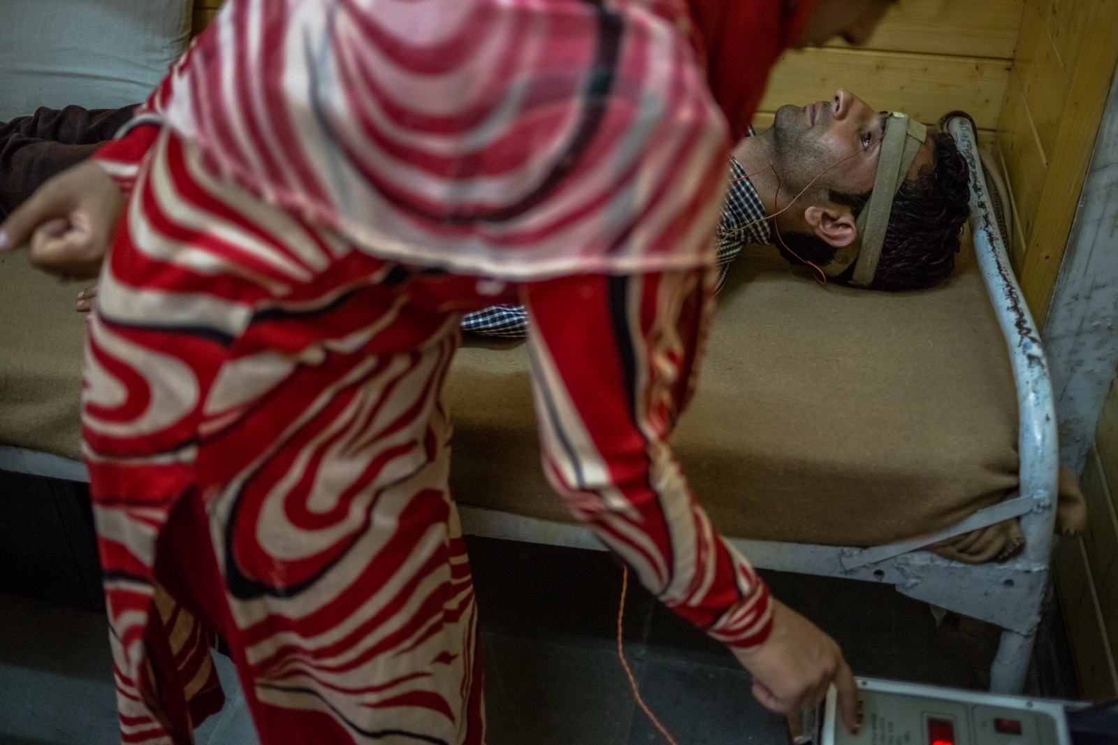 A Kashmiri patient who has been suffering from symptoms of depression and anxiety undergoes a form of electro-convulsive therapy by a member of medical staff at the Psychiatric Diseases government hospital in Srinagar on September 14, 2015.