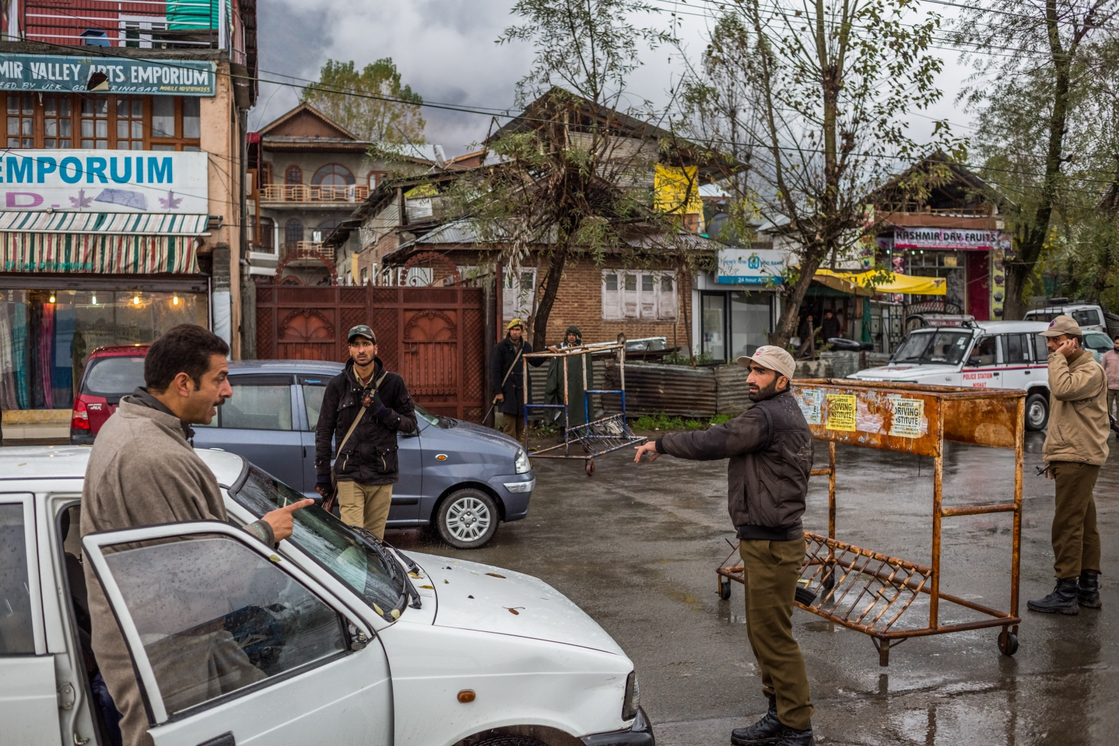 A Kashmiri driver (L) reacts as he is questioned and told by Jammu and Kashmir police personnel that his car will be searched by Indian security personnel at a checkpoint in Srinagar on November 4, 2015.