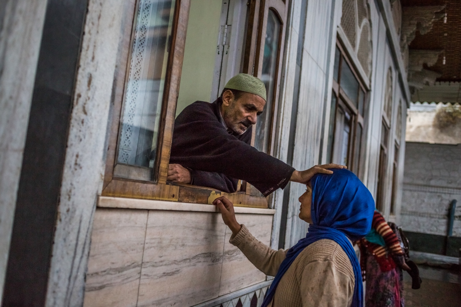 A Kashmiri 'pir', or faith healer offers prayers as he blesses a woman inside the Makhdoom Sahib Shrine in Srinagar. Many Kashmiris seek solace in shrines dedicated to auspicious saints or put their trust in faith healers, who bless potions and offer recitations or amulets thought to bring powers of protection.
