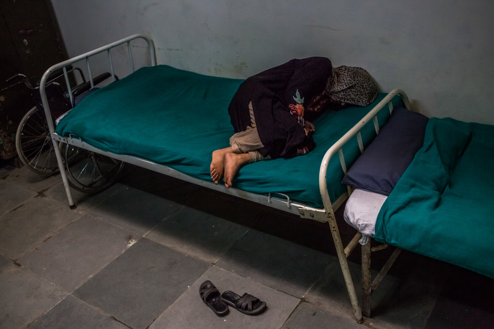 Kashmiri patient Masrat Naz, 45, and who is suffering from symptoms of schizophrenia, lies on a bed as she periodically shouts to medical staff after being brought by relatives to the casualty ward at the Psychiatric Diseases hospital in Srinagar on November 20, 2015.