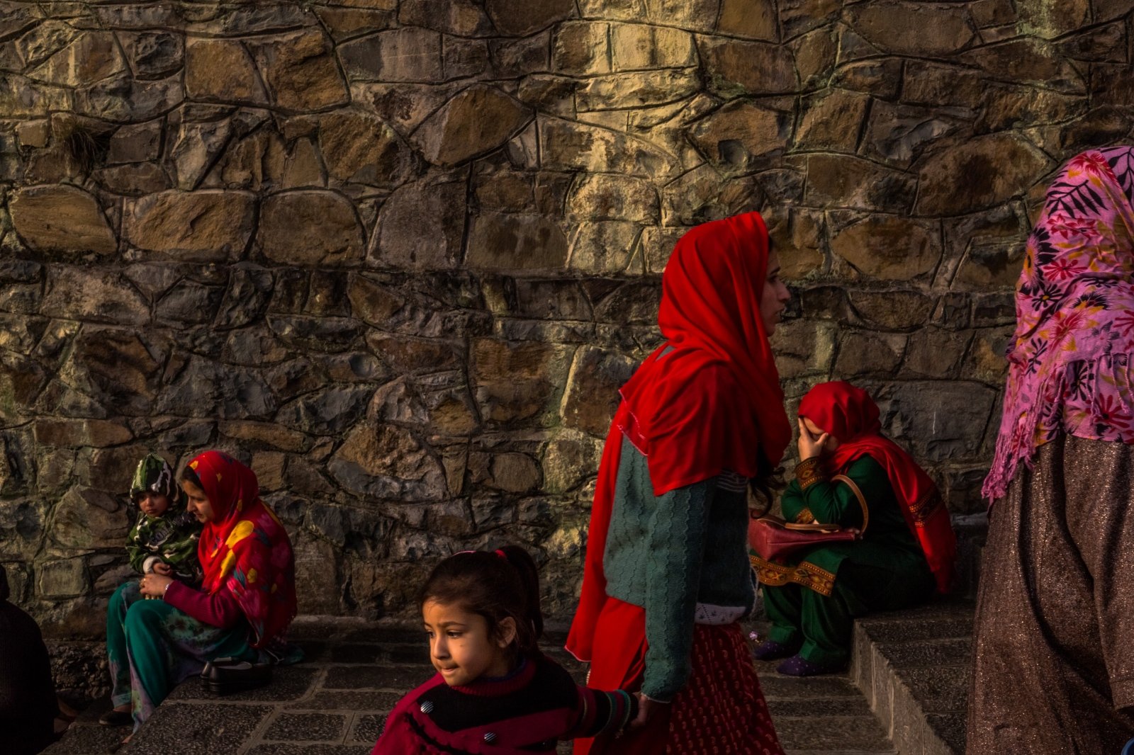 A Kashmiri woman prays on the steps of the Makhdoom Sahib Shrine as others arrive in Srinagar. Many Kashmiris seek solace in shrines dedicated to auspicious saints or put their trust in faith healers, who bless potions and offer recitations or amulets thought to bring powers of protection.