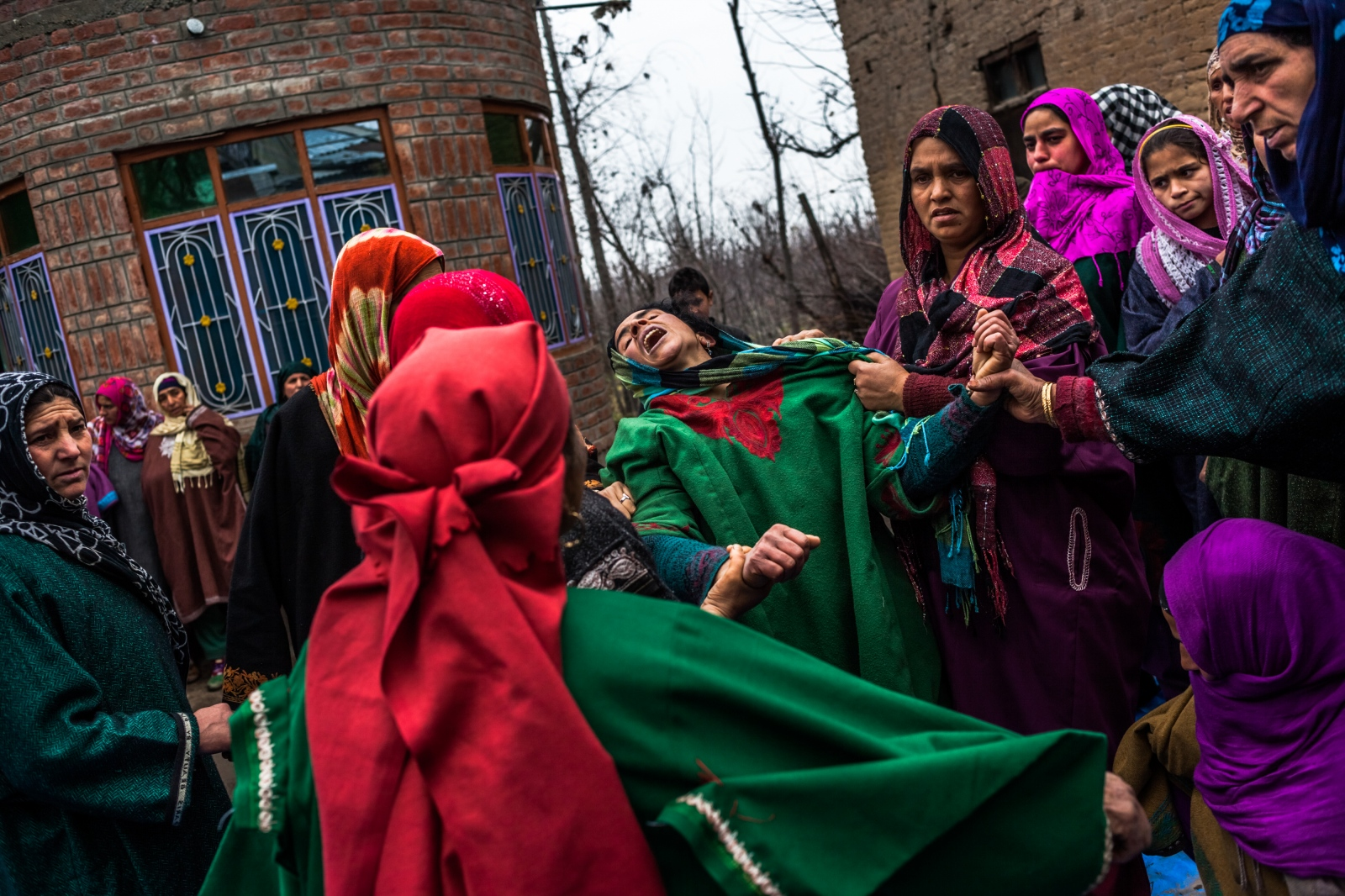 Kashmiri relative Hafeeza Khan (C), weeps during the funeral of nephew Rasiq Ahmed Khan, aged around 22, and who was found shot to death, at their home in Watchohallan village in south Kashmir's Shopian district some 80 kms from Srinagar on December 14, 2015. Raisq, who disappeared on December 13, was found shot to death by gunmen who local residents report were members of the Indian police Special Operations Group.