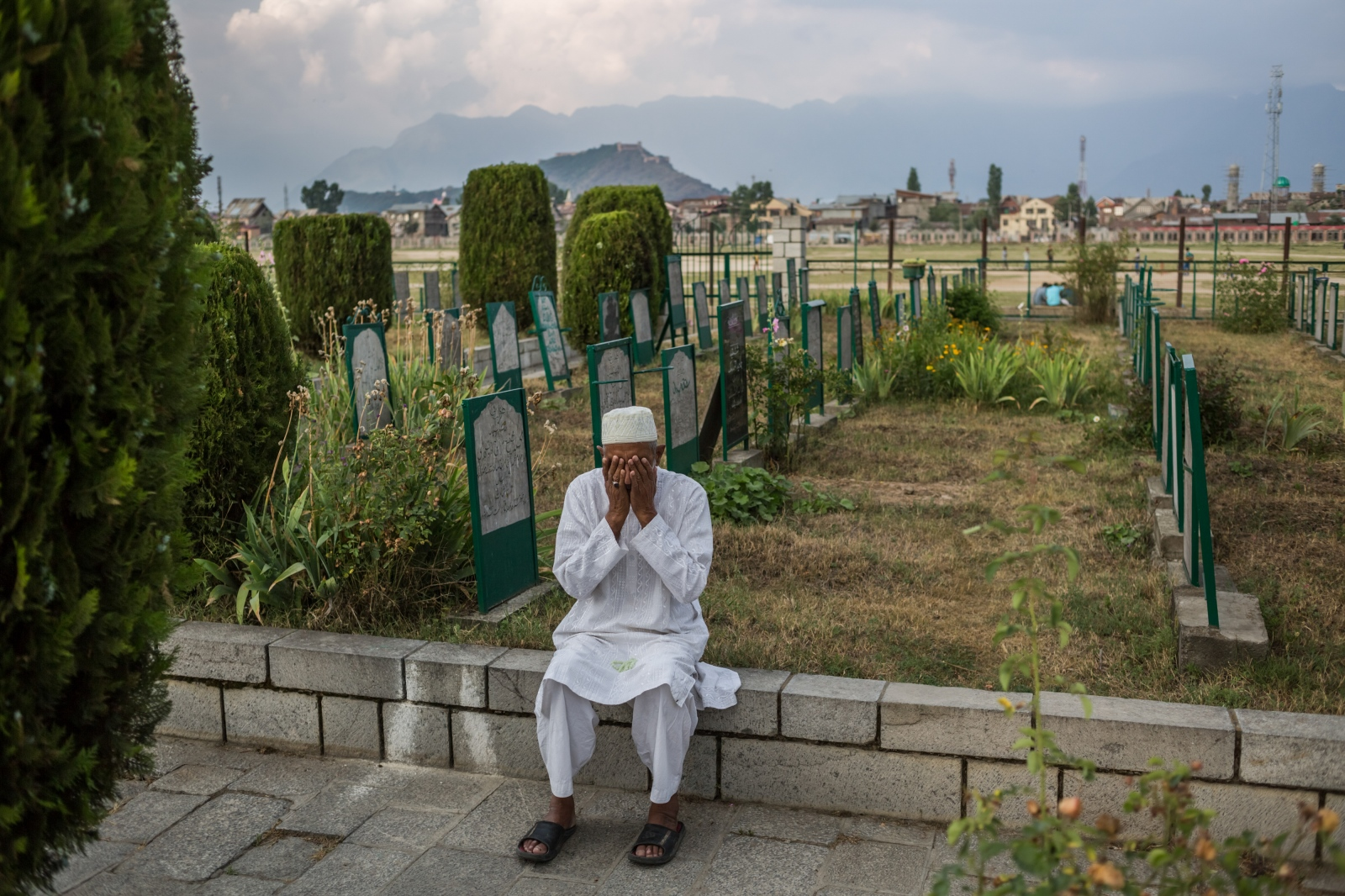Kashmiri resident Hamidullah Khan, 65, wipes his hands over his face after singing a prayer at the Martyrs' Graveyard in the Eidgagh area of downtown Srinagar on June 11, 2016. Khan lives in Eidgagh and comes to the graveyard almost every day, to offer prayers for those killed in Kashmir's unrest and help tend to the area.