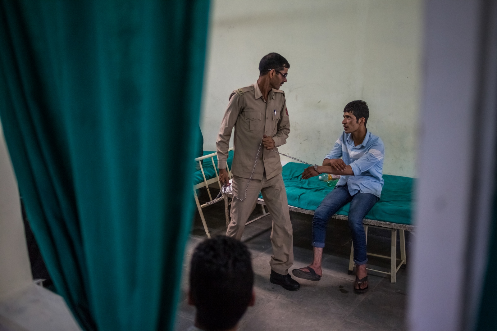 A Jammu and Kashmir police personnel tugs at a chain attached to handcuffs restraining Kashmiri resident Arsalan Mushtaq, 20, as they prepare to leave the casualty ward at the Psychiatric Diseases government hospital in Srinagar on June 13, 2016. Mushtaq was arrested following a disturbance at his home the evening before, and brought to the hospital for assessment. Police personnel with him said he was both a drug addict and a stone-pelter and was due to be brought before a court later that day. Mushtaq kept repeating that he was 'mentally and physically fit'.