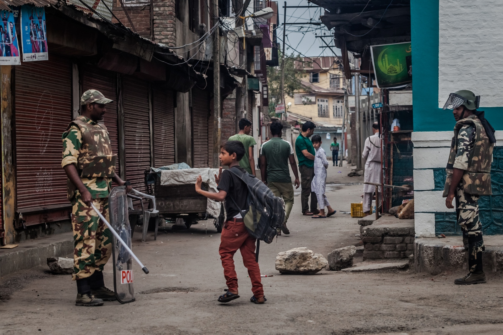 A Kashmiri child gestures as he walks past Indian Central Reserve Police Force (CRPF) personnel standing guard during a strict curfew in downtown Srinagar on July 22, 2016.