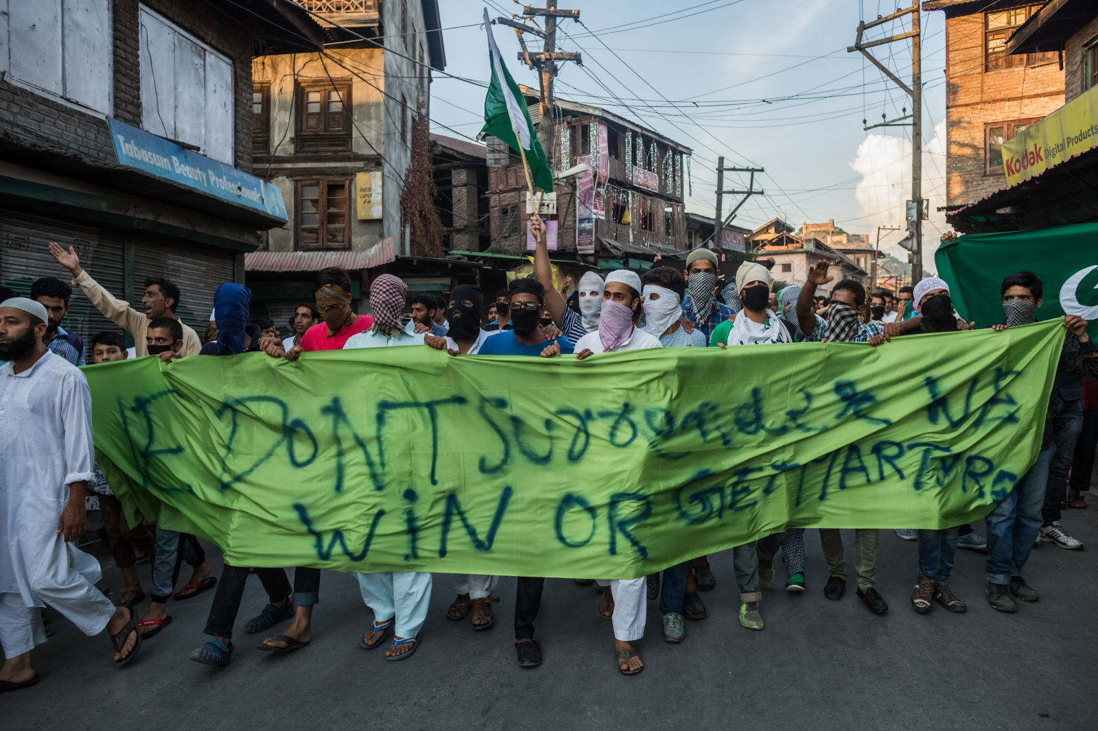 Kashmiri demonstrators carry a banner that reads, 'We don't surrender, we win or get martyred' through downtown Srinagar on August 12, 2016. Peaceful protests, often organised locally, see demonstrators chanting slogans and carrying banners, led by a small group to ensure order. Some lead clashes with Indian security personnel who disallow these types of gatherings.