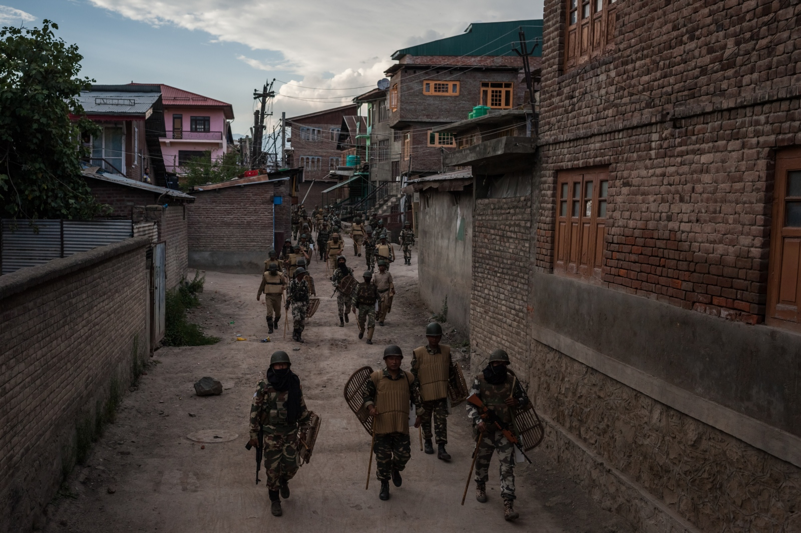 Indian Central Reserve Police Force (CRPF) and security personnel retreat following a day of curfew and shutdown in downtown Srinagar on August 18, 2016.