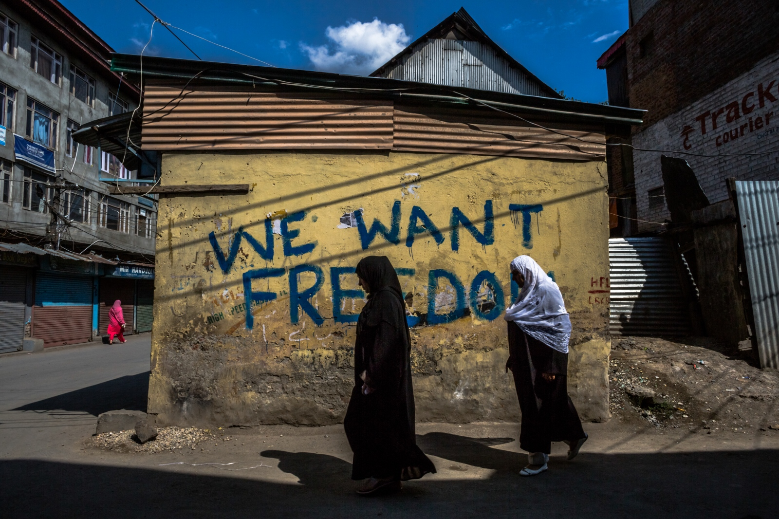 Kashmiri residents walk past graffiti reading, 'We want freedom' during a curfew and shutdown in downtown Srinagar on September 12, 2016.