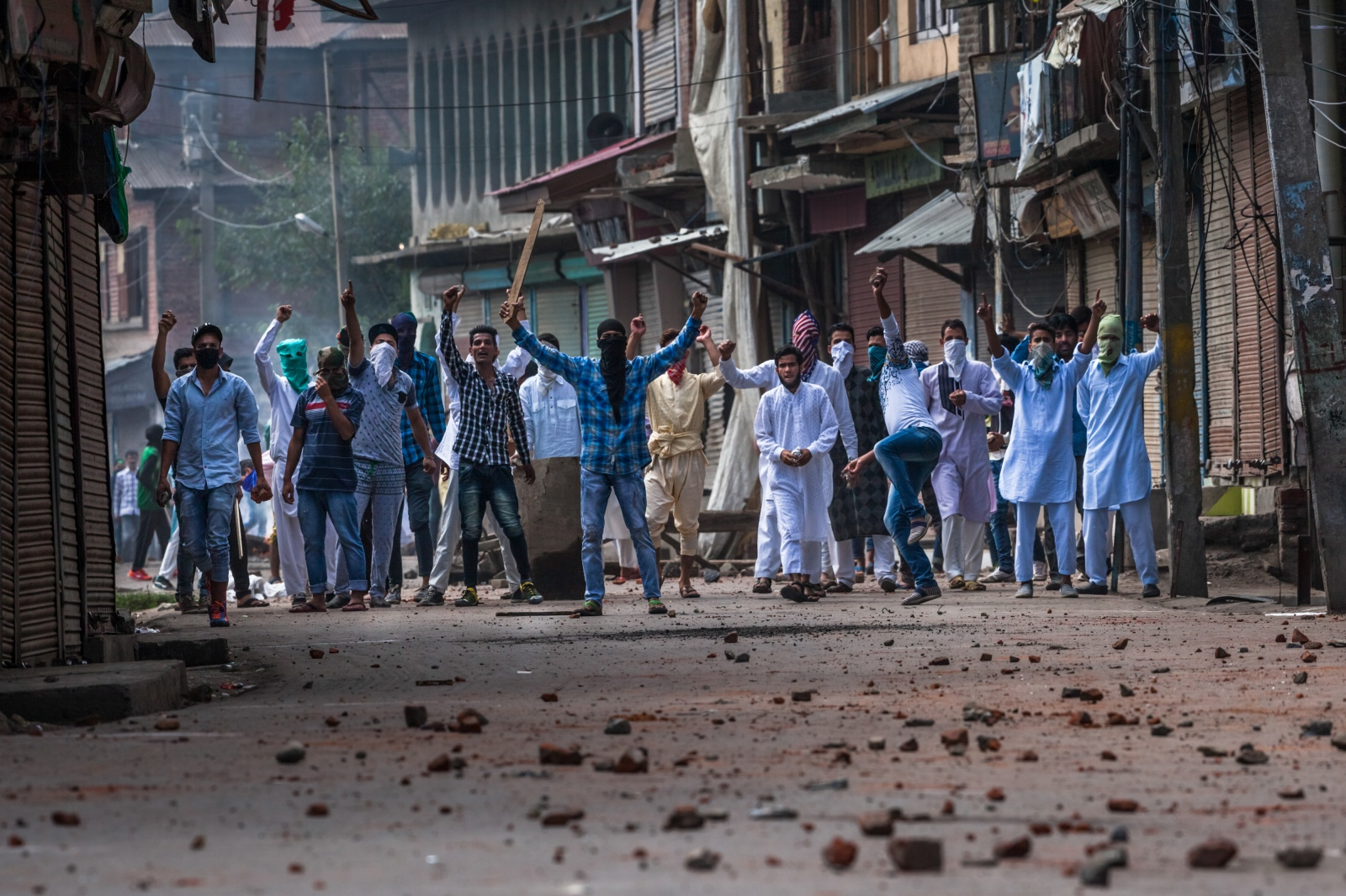 Kashmiri protesters shout slogans and throw stones during clashes with Indian Central Reserve Police Force (CRPF) and security personnel during a strict curfew on Eid-al-Adha, one of the most important religious festivals in the Muslim calendar, in the Batamloo area of Srinagar.