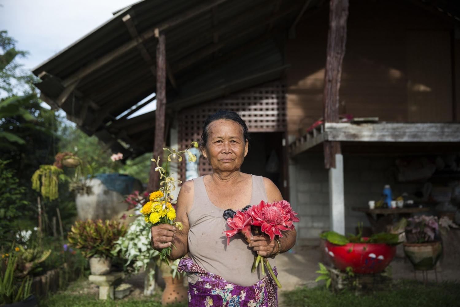 Rattana Seli, 66, holds flowers she grew in her garden outside a neighbours house.