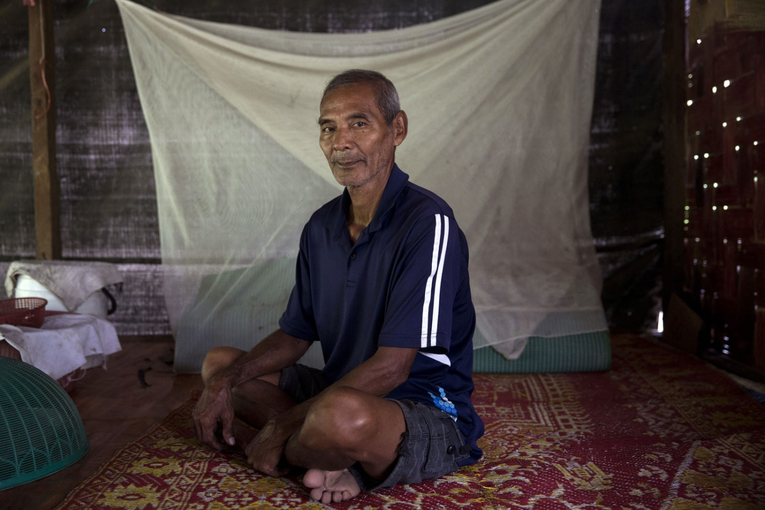 Pasit Bunban, 67, sits where he sleeps with his mosquito net hanging behind.