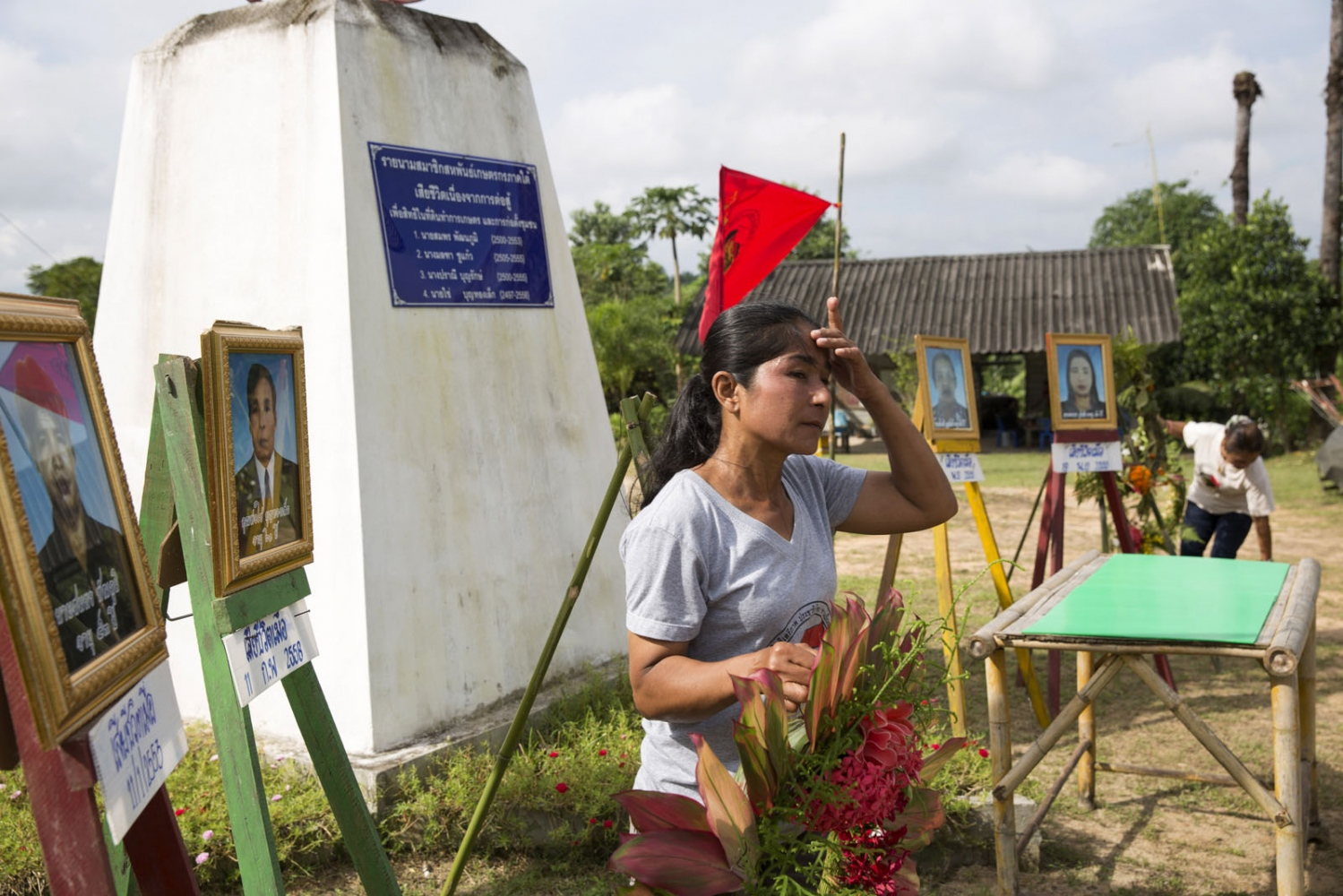 A member of the Klong Sai Pattana community wipes her brow as she helps set-up for the annual memorial day event. Occurring on November 28th the villagers use the event to remember each of the four people murdered during their prolonged fight to remain on the land. for each of the four people murdered during their prolonged fight to remain on the land.