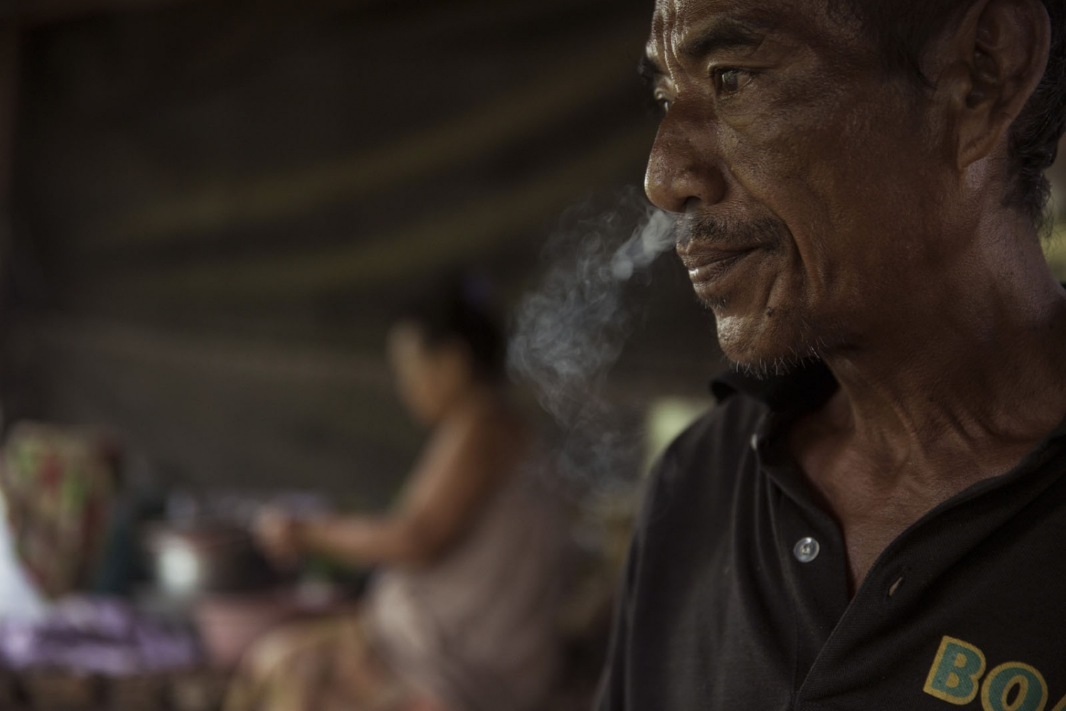 Sukon Dongwun, 54, smokes a cigarette in a neighbours house.