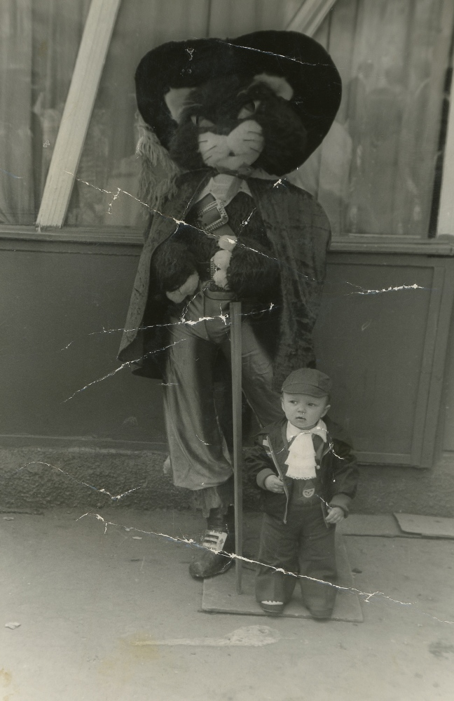 Nina's son Pavel stands next to a costumed...