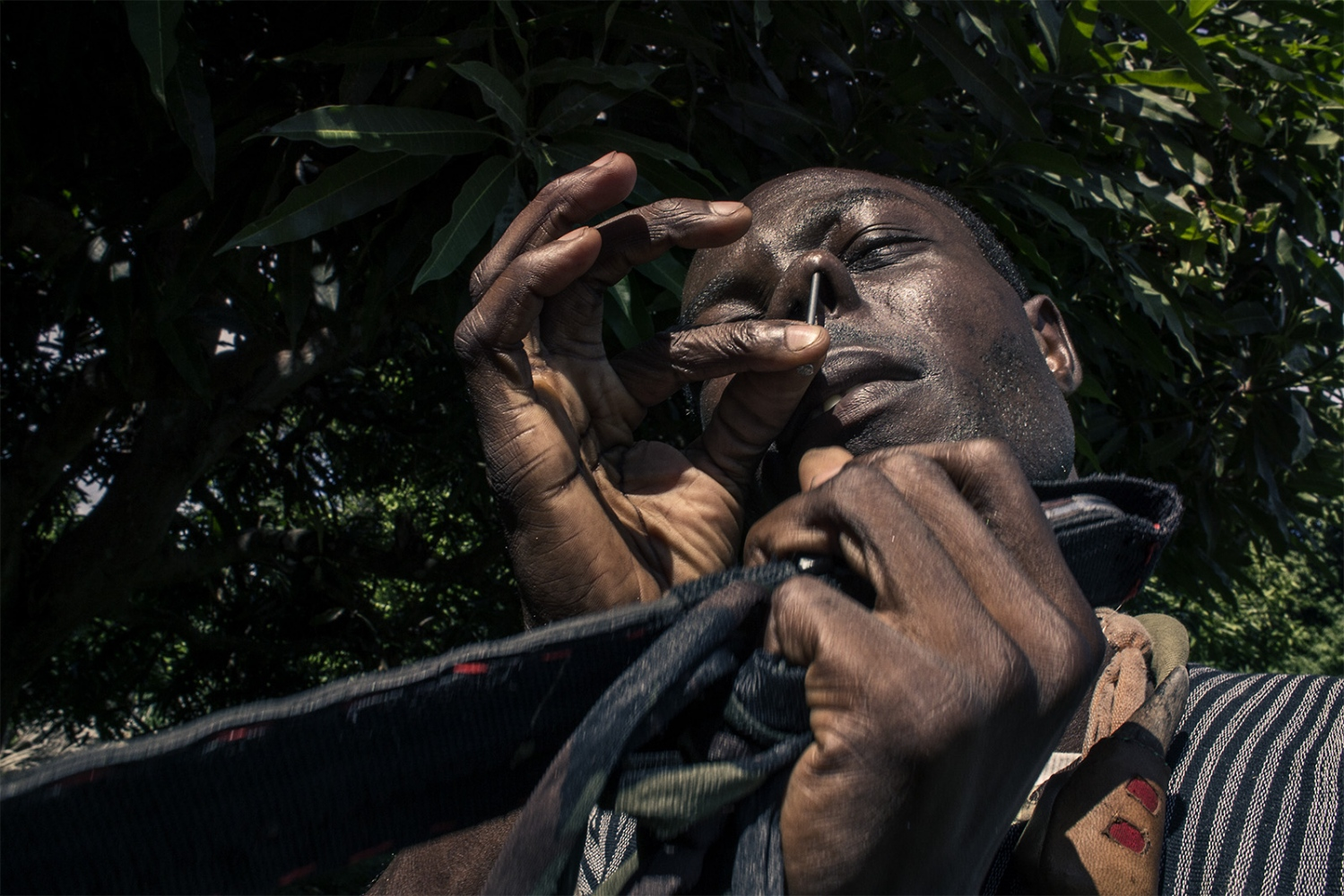 Enrique is the official Marabout of the area, so he's a leader, healer and protector. He's demonstrating his physical strength pushing a nail in his nose.