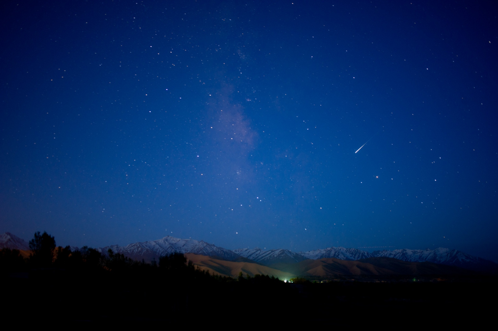 A meteor passes by a faint Milky Way over the Hindu Kush mountains in Afghanistan.
