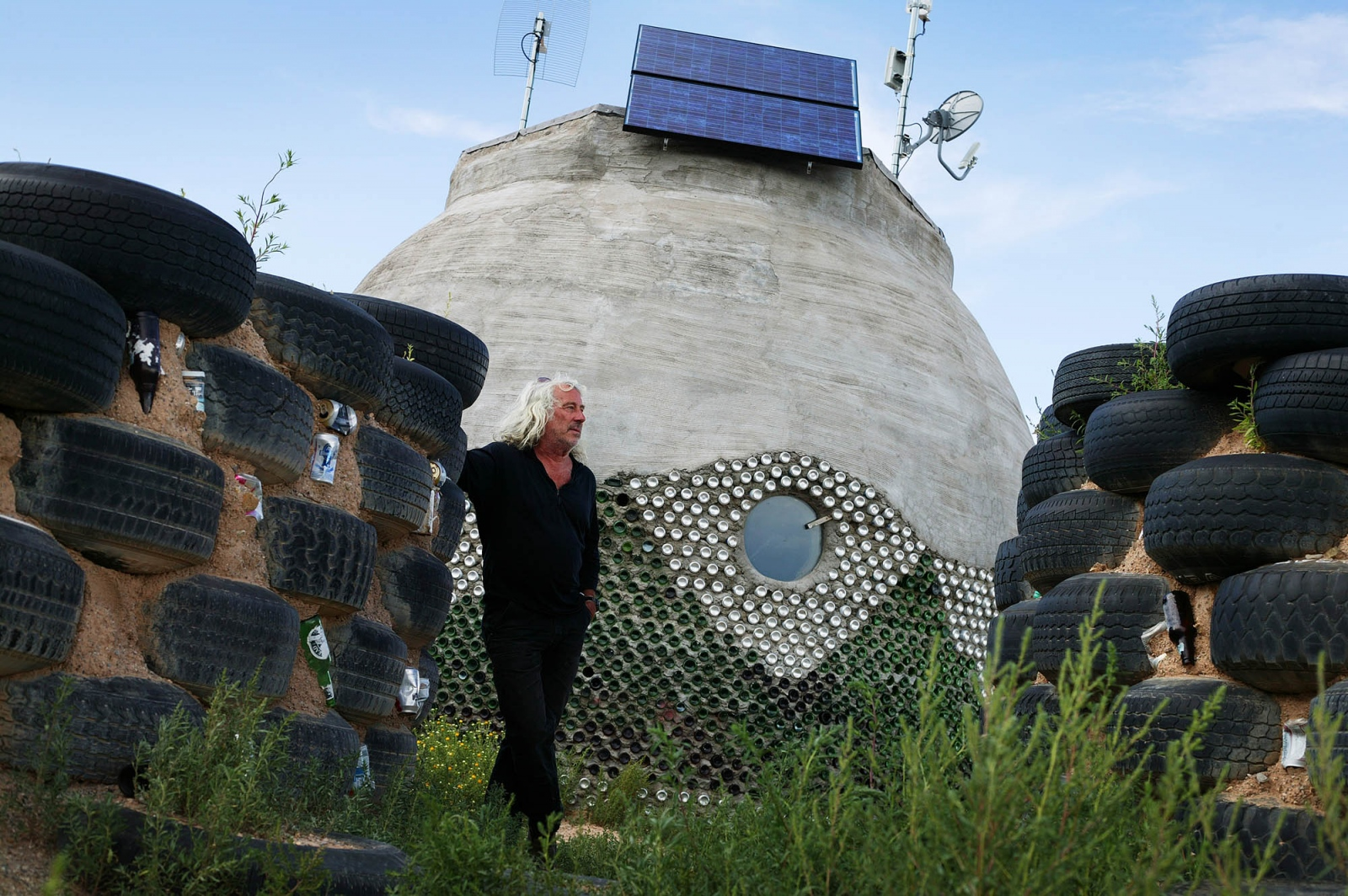 Eco Architect Michael Reynolds with one of his off-the-grid Earthship homes, made of recycled tires.