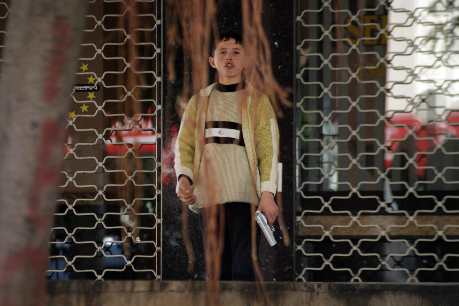 Boy with cigarette and toy gun, Mersin, Turkey