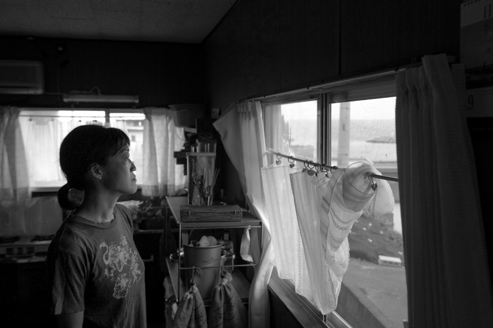 Ijikacho, Toba, Aiko Ohno, 37, inside her house in ijikacho, Toba, Mie prefecture, watching outside the window