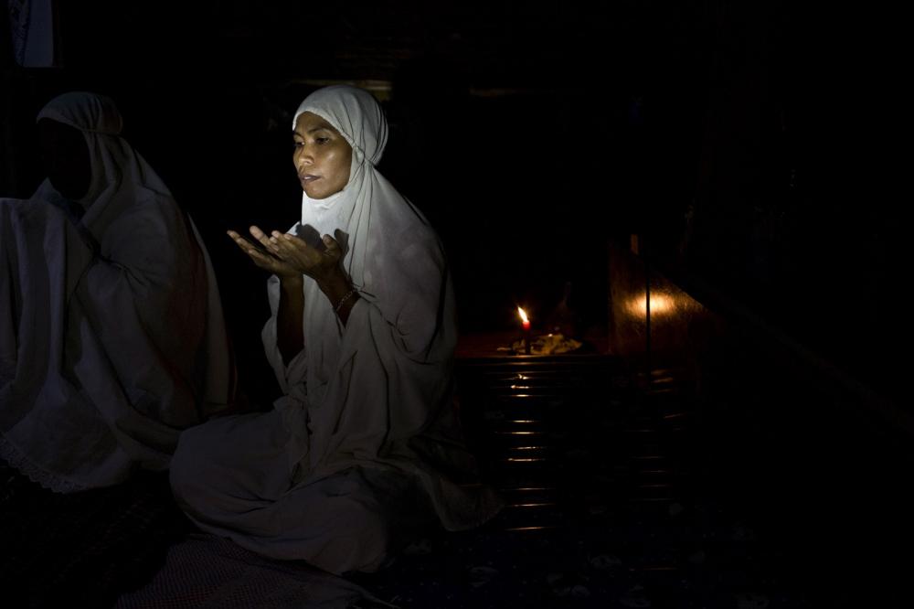 Janya Ruangthong, 36, originally from neighbouring Krabi province prays in her house. Her family is one of five Muslim familes living in Klong Sai Pattana. Surwat Thani, Thailand.