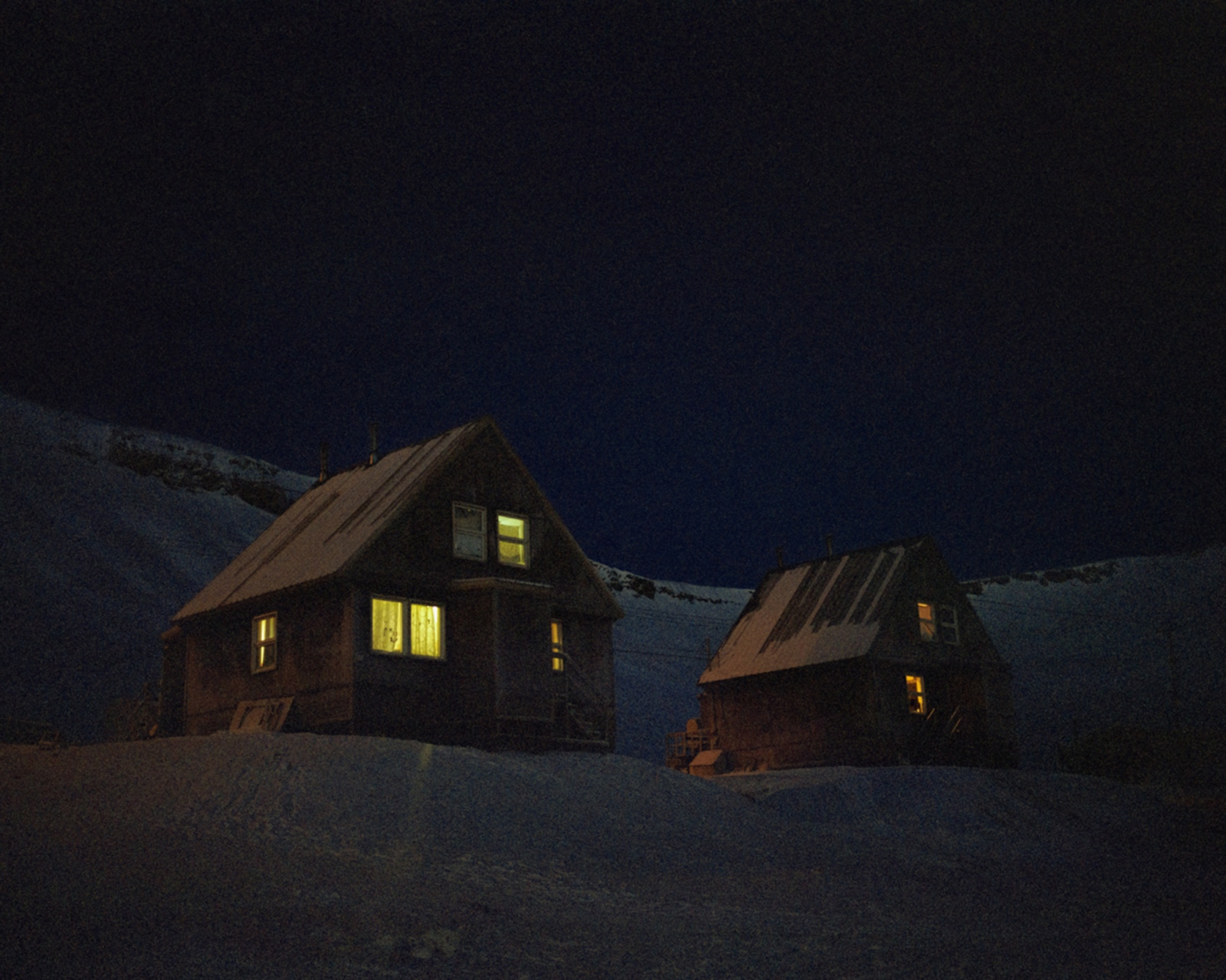 Houses in Arctic Bay glow in the darkness of a December afternoon.
