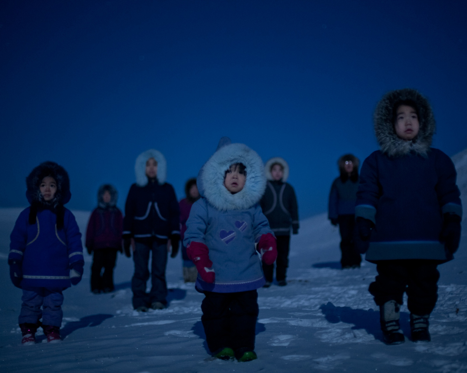 The Tatatoapik family takes in the light of a particularly bright full moon in February. In the depths of winter, it is safe to drive a truck or SUV out onto the sea ice and into the mountains, as the family had done for this occasion.