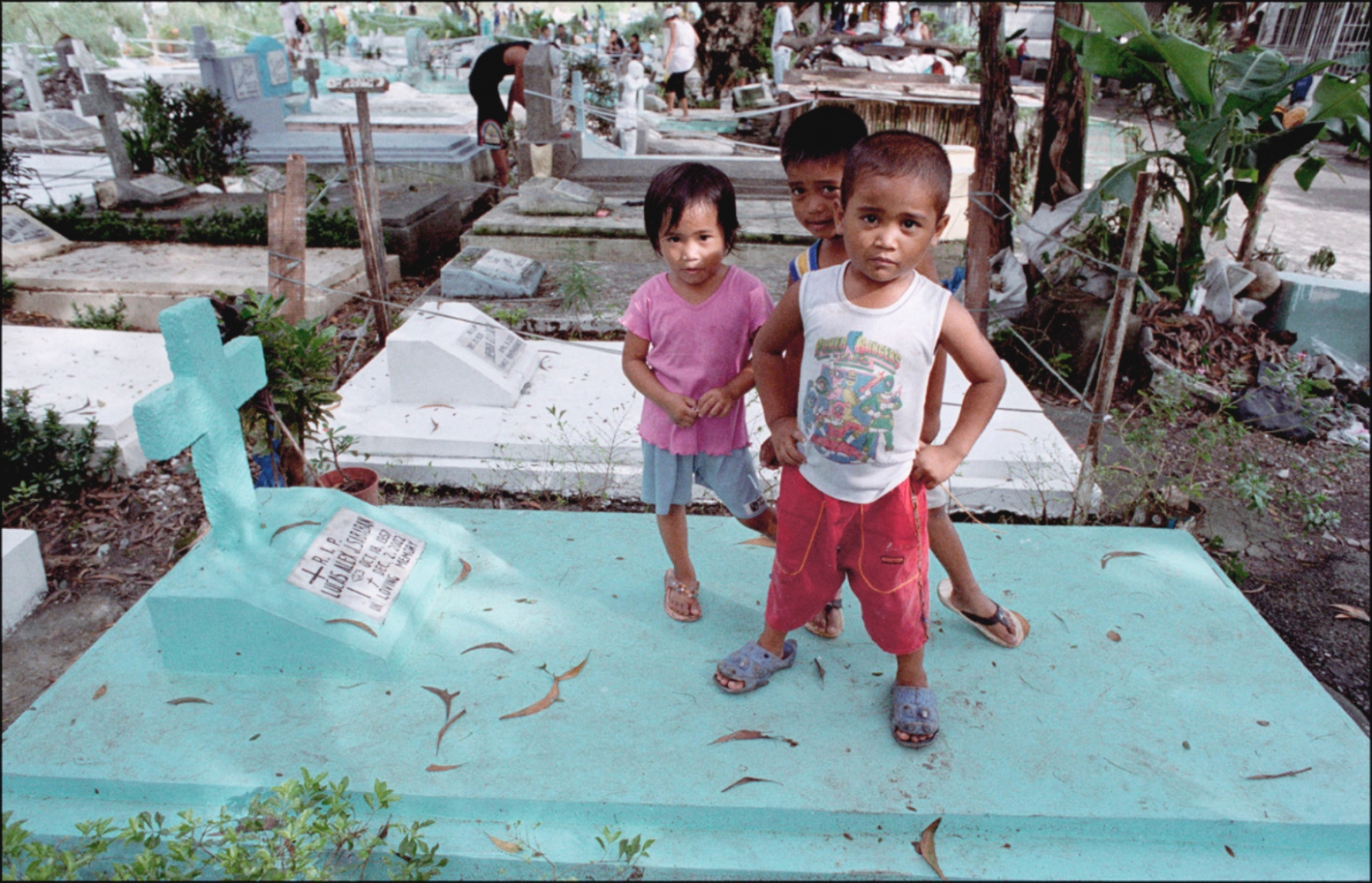 Three Children Standing on Grave, South Cemetery, Manila, Philippines, November 2005