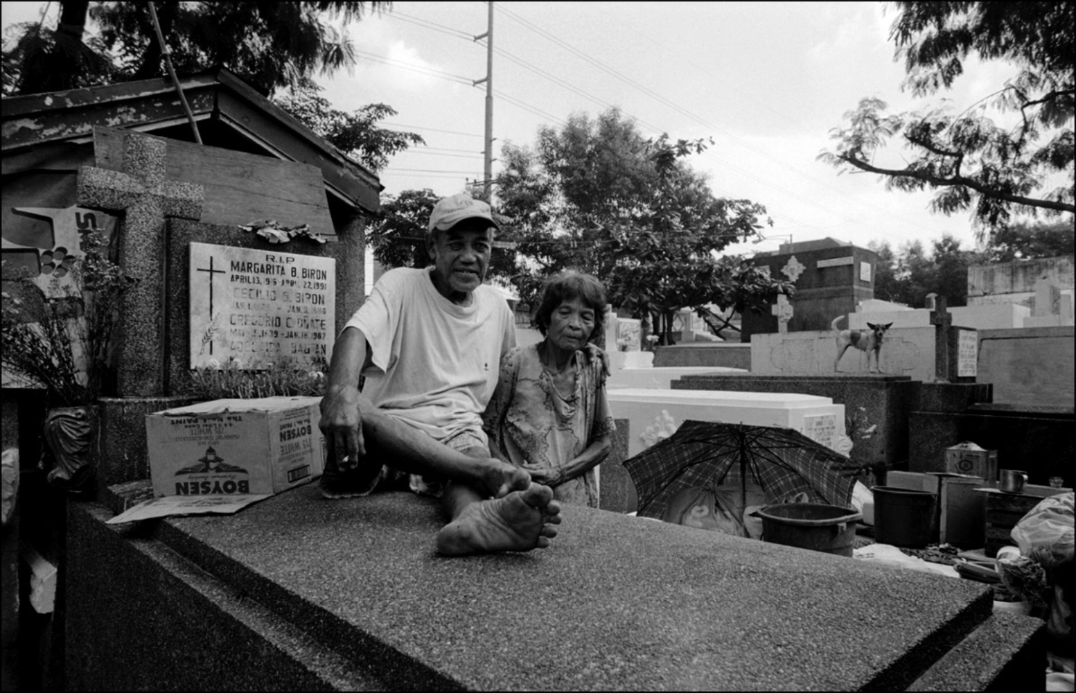A Man Sitting on Tomb by His Wife, South Cemetery, Manila, Philippines, November 2005