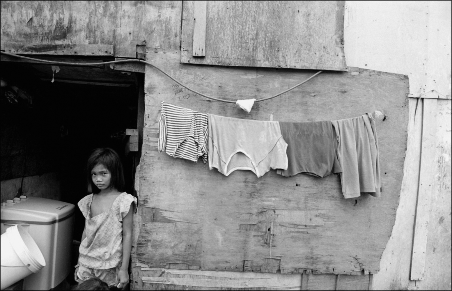 Girl Standing by Hanging Shirts, San Andrea Bridge, Manila, Philippines, November 2005