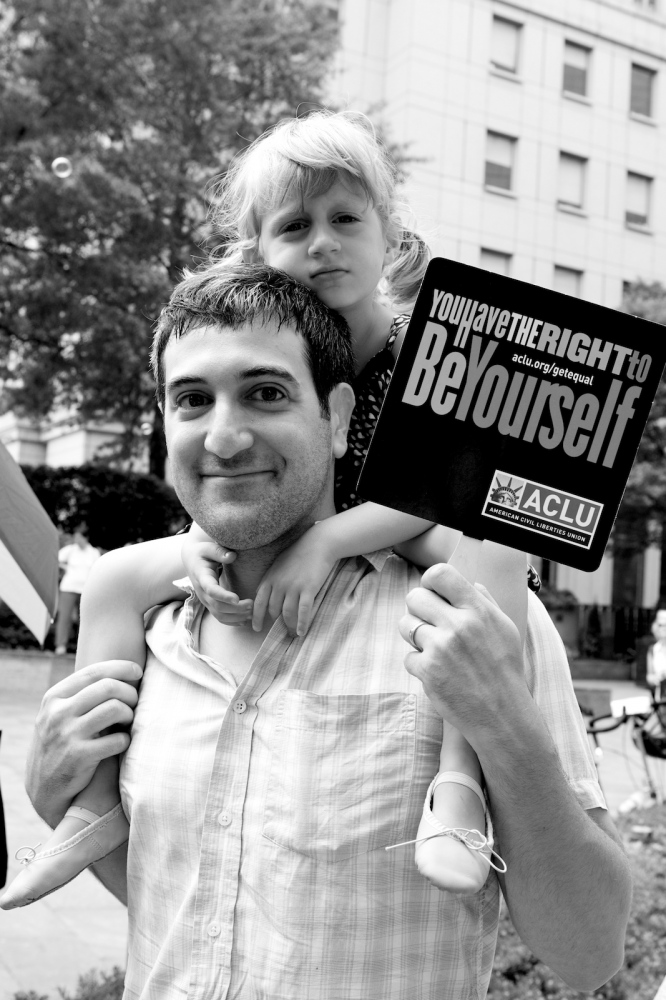 "A man and child hold a ""You Have the Right to Be Yourself"" sign outside the Manhattan City Clerk's office, on the first day New York State's Marriage Equality Act goes into effect. New York, NY, July 24, 2011"