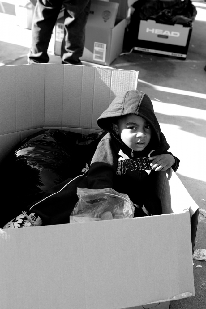 A young boy sits in a box at a clothing and food distribution center in Breezy Point, Queens, N.Y. on Nov. 11, 2012. The tiny beachfront town, with many firefighters as its residents, was told to evacuate before Hurricane Sandy hit New York. Rising sea water made its way into electrical systems causing a fire that destroyed more than 120 homes.