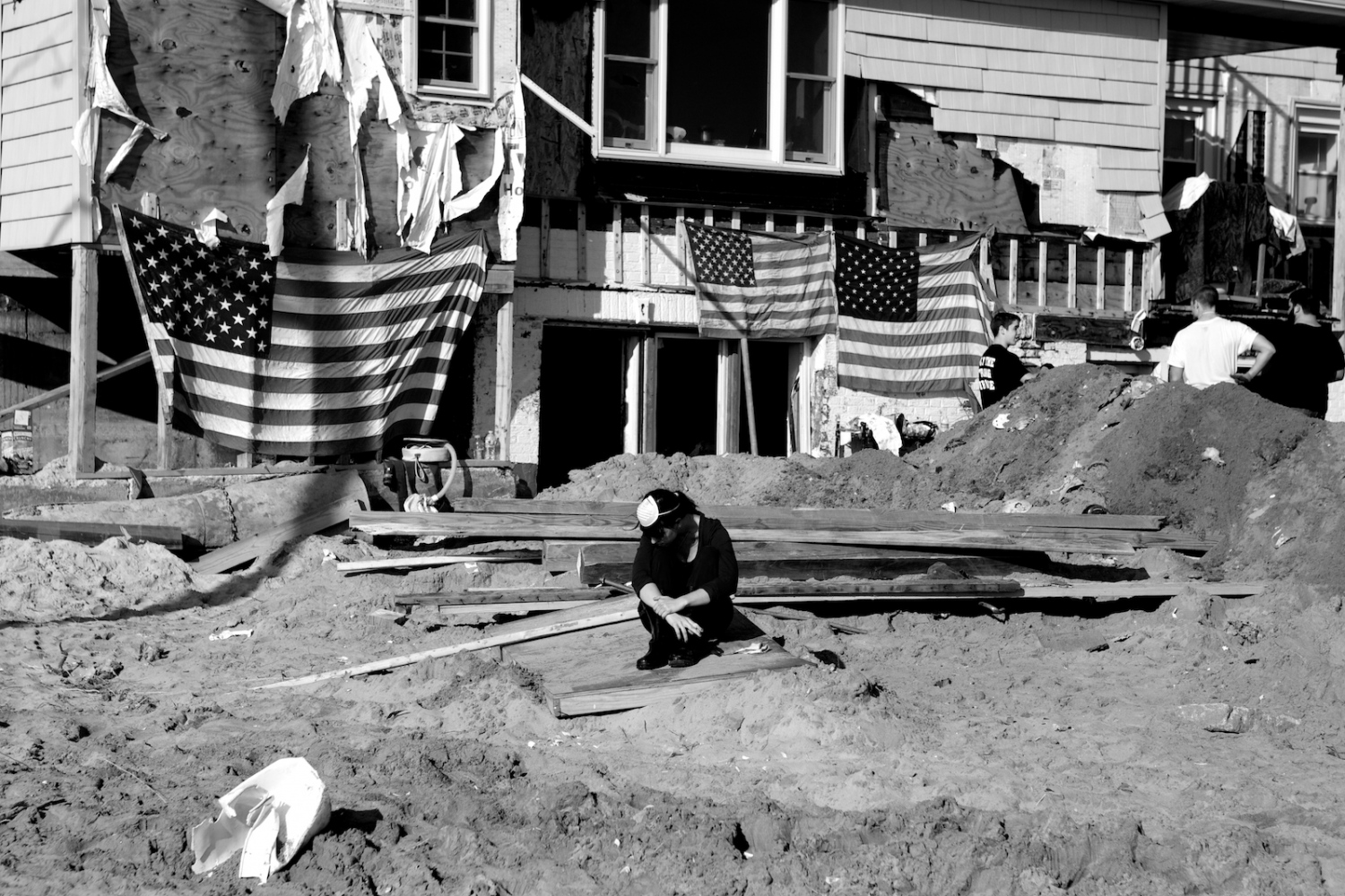 A woman sits in front of a home destroyed by Hurricane Sandy in Breezy Point, Queens, N.Y. on Nov. 11, 2012.