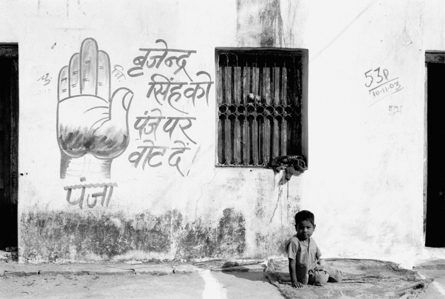 Boy by Drawing of Hand on Wall, Okhra, India, November 2003