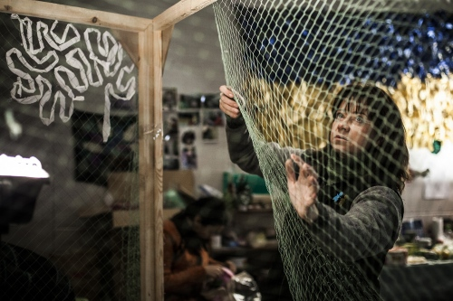 The net battalion. A volunteer woman sewing a mimetic net in a basement of an abandoned mall.
