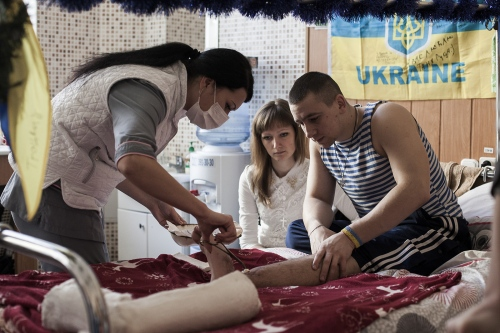 Volunteer nurse is taking care of a wounded soldier in the military hospital in Kiev
