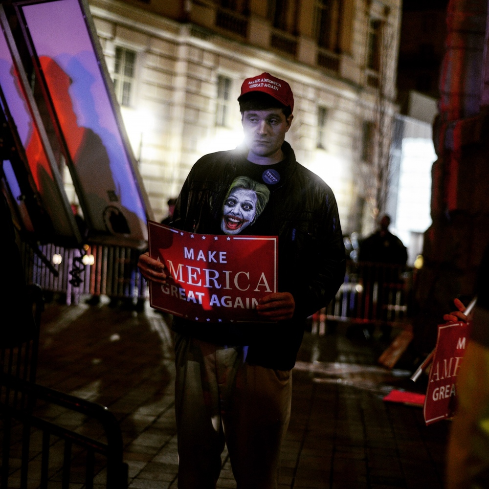A trump supporter outside the president's hotel, which is now in violation of its lease and possibly federal law. Protesters clashed with a small group of supporters there last night.