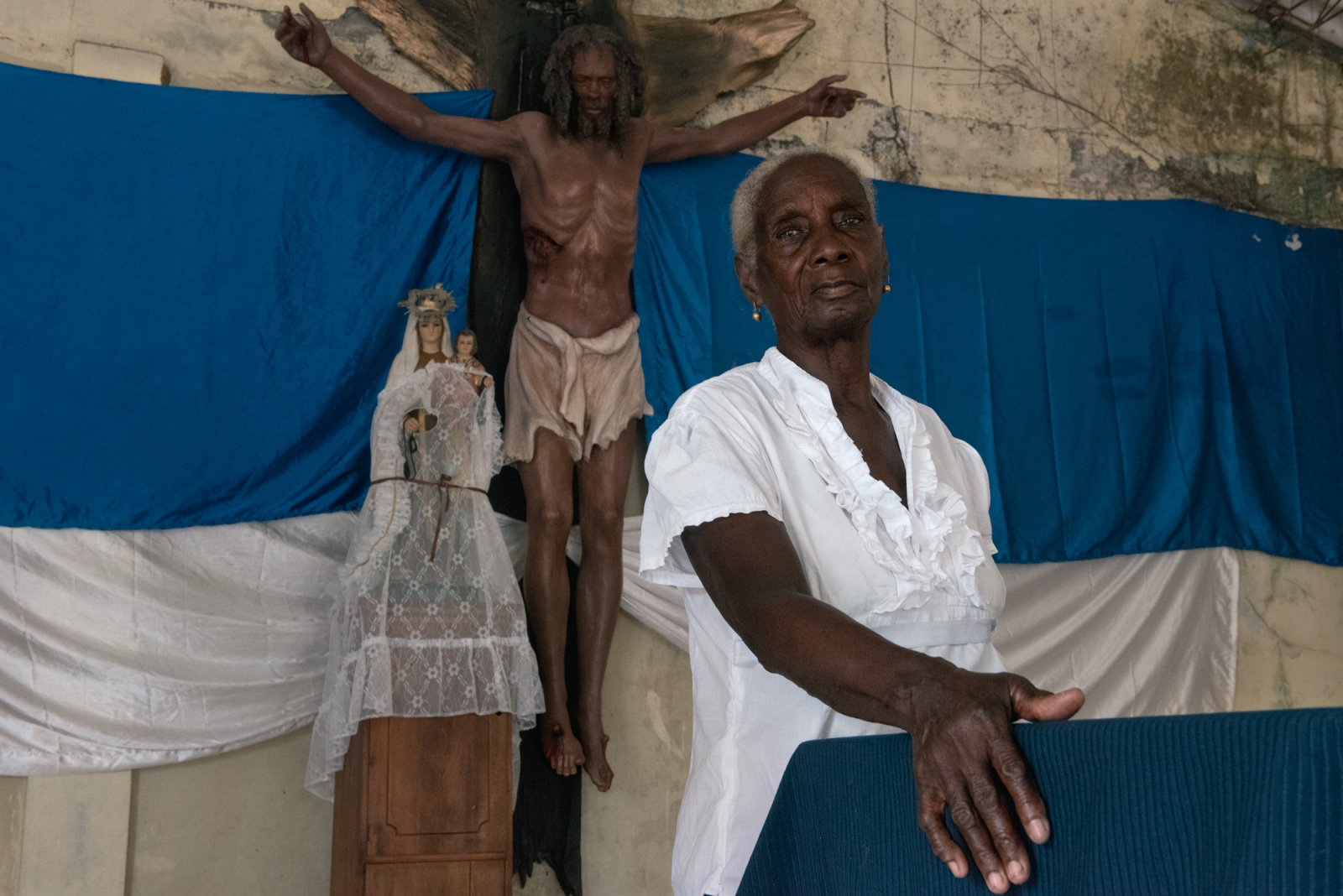 Ceneida Mena poses for a portrait in front of a black Christ that the FARC gifted to New Bellavista. However, the Christ was not well received in town and it had to be taken to La Loma where residents agreed to receive it in their church. Ceneida's son was the first victim of paramilitary violence in La Loma, he was killed in a bar. She still does not know the reason why they killed him. She believes that the FARC should repair the damage they have done in more concrete and less symbolic ways.