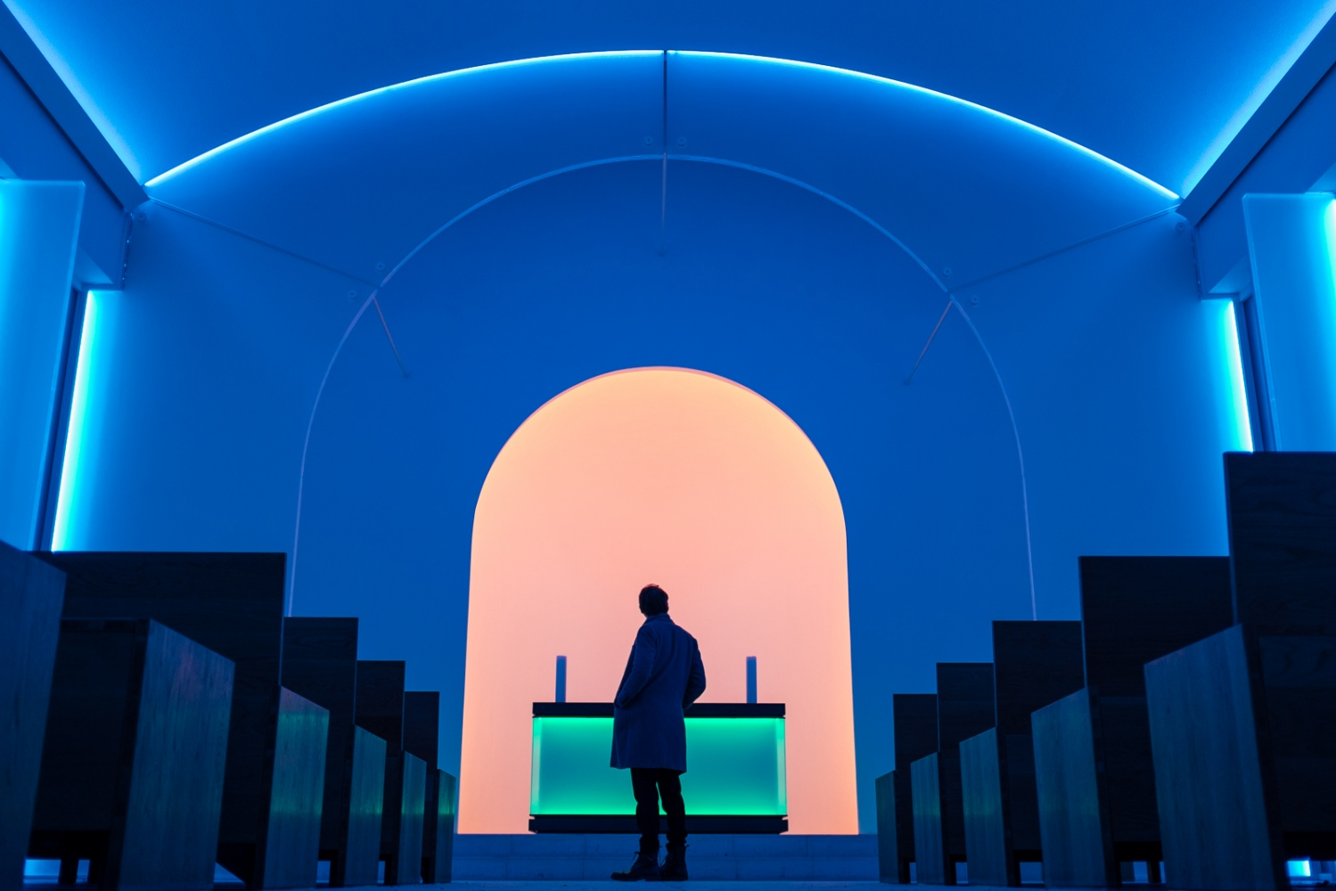 Berlin, GERMANY, January 21, 2017: A visitor observes the light installation by James Turrell, the infamous American light artist, in the chapel of Dorotheenstädtischer Cemetery in Berlin. The exhibition occurs during the blue hour just before dusk. Turrell plays with the concept of biblical light: starting with blue light, the chapel is slowly filled with pinks, oranges and reds, mimicking that of a real sunset.