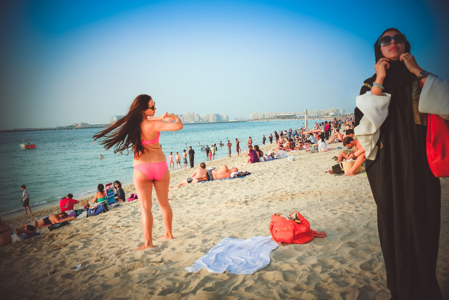 Dubai, UAE, March 21,2014: 'Culture Clash'. A beach scene at Dubai's JBR beach.