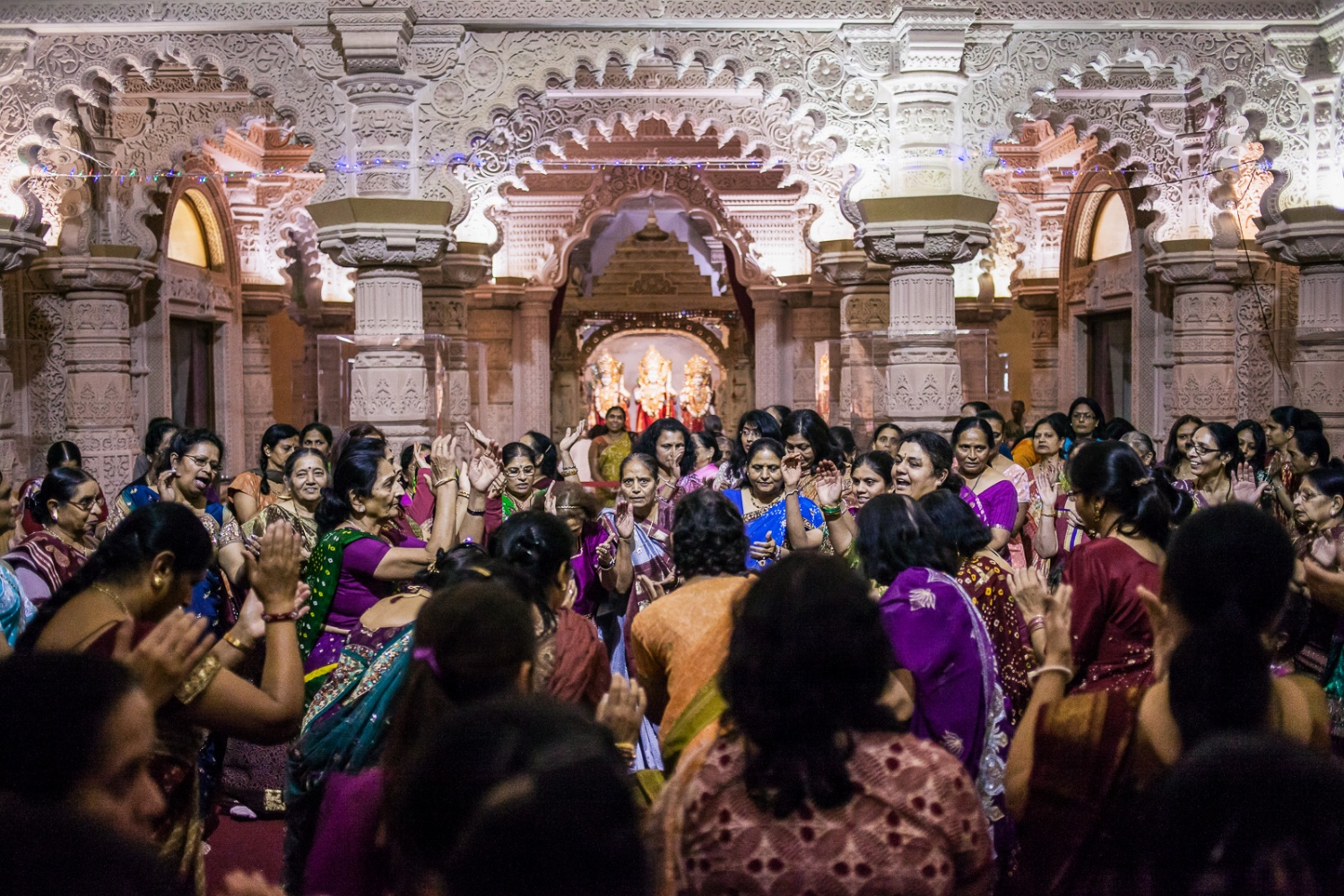 "London, UK, October 22, 2012: Hindu devotees sing and dance during Diwali festival celebrations at Shri Vallabh Nidhi temple. The ""festival of lights"" is one of the most important Hindu celebrations. Devotees come together to perform traditional dances and rituals, such as the lighting of small clay lamps filled with oil to signify the triumph of good over evil."