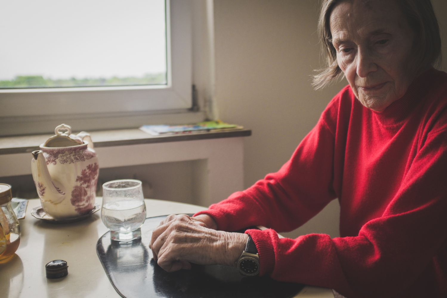 'Yielding'. Helga sitting in her kitchen, while her daughter Nicoletta finalises preparations for the departure to the retirement home. Neuss, GERMANY, May 29, 2015.