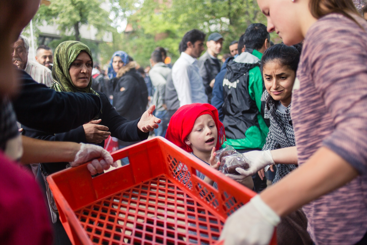 "Berlin, GERMANY, September 9, 2015: Volunteers from Berlin's citizen initiative ""Moabit hilft"" hand out food to refugees waiting to seek asylum at LaGeSo (regional office for health and social affairs). 