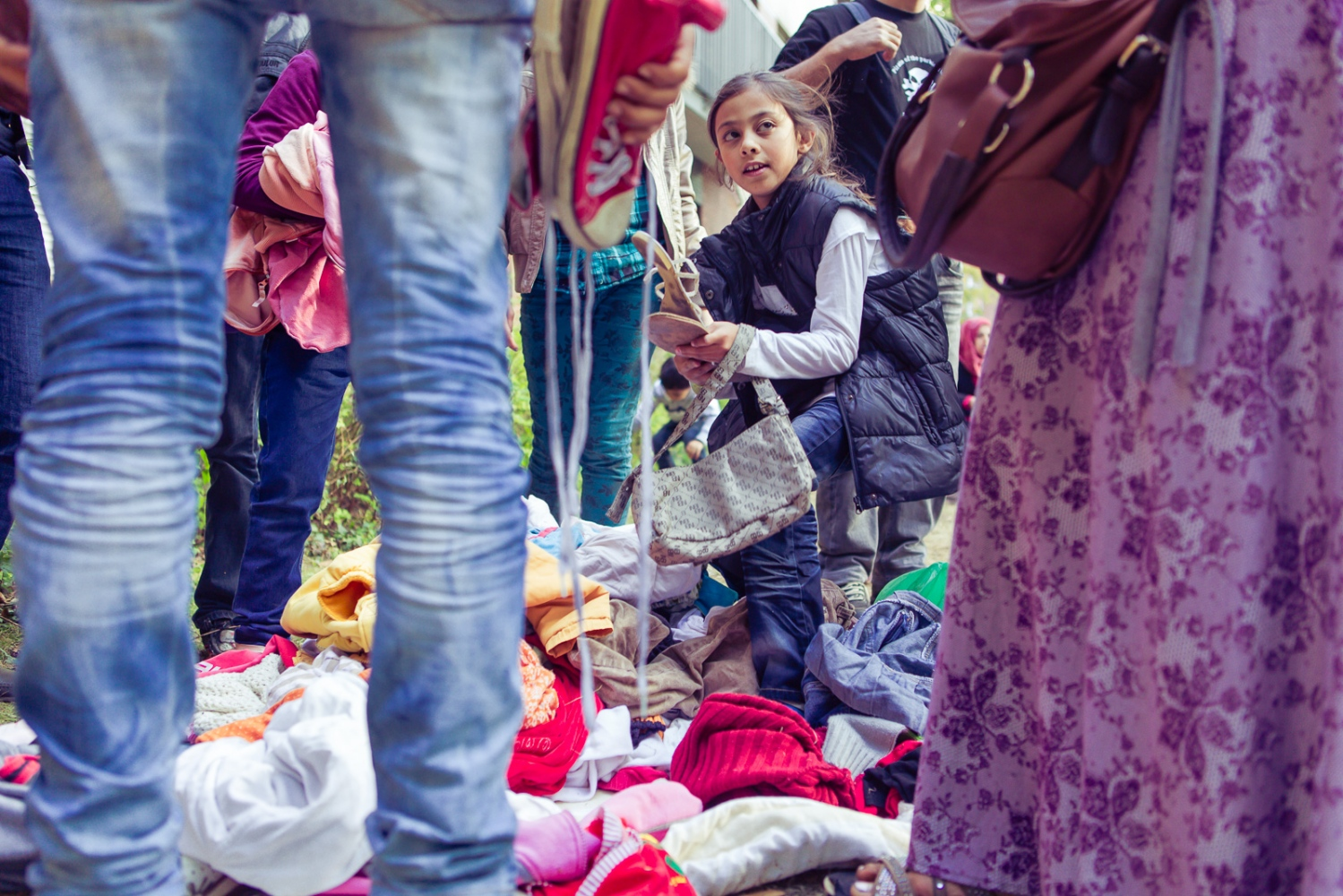 "Berlin, GERMANY, September 10, 2015: Refugees go through donations whilst waiting at LaGeSo (regional office for health and social affairs). The clothes were collected by volunteers from Berlin's citizen initiative ""Moabit hilft""."