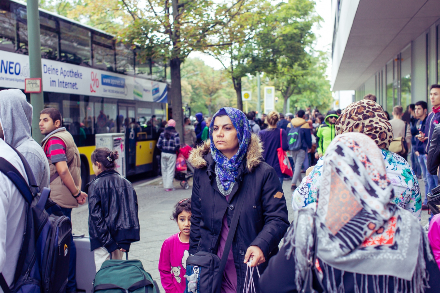 Berlin, GERMANY, September 9, 2015: Refugees wait for designated buses to shuttle them to temporary shelters after waiting all day at LaGeSo (regional office for health and social affairs).