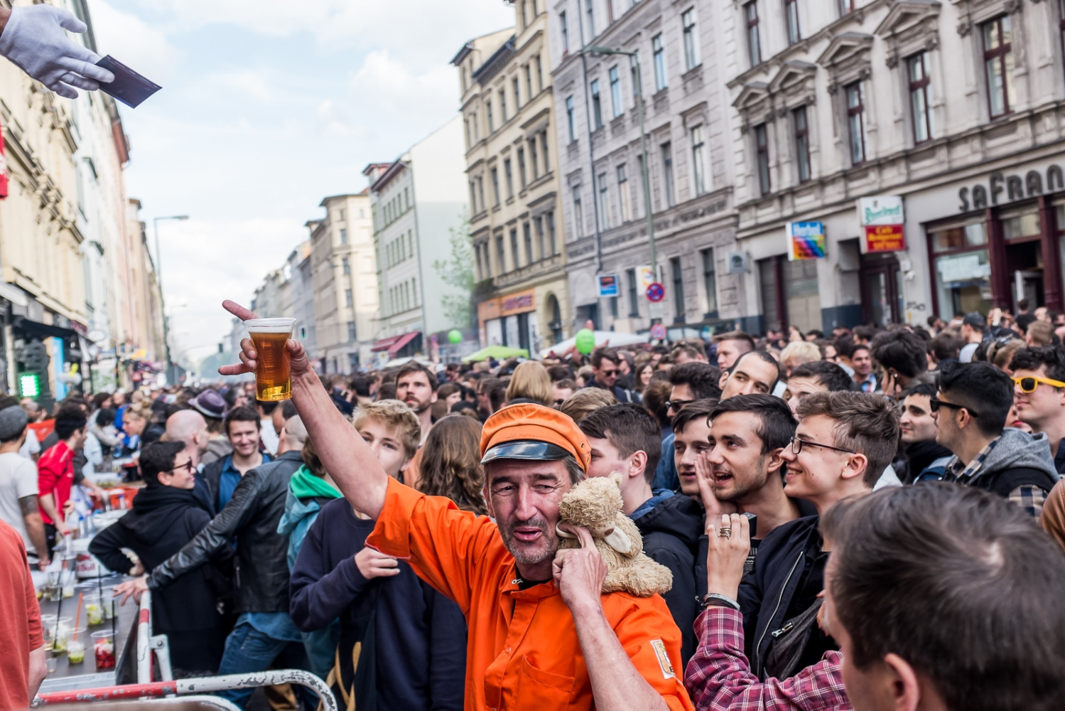 Berlin, GERMANY, May 1, 2015: May Day celebrations in Oranienstrasse, Kreuzberg. For an entire day most of Kreuzberg SO 36 district is cordoned off to allow people to mingle, drink, and dance through the streets during MyFest. In recent years, May Day has been rather peaceful. However, at times there are still riots, with leftwing youth throwing rocks and bottles, smashing windows, setting cars on fire, and getting into fights with the police. The riots originated in May 1, 1987, when a fight between young autonomists who fought for anticapitalist change and the police first took place on a grand scale.