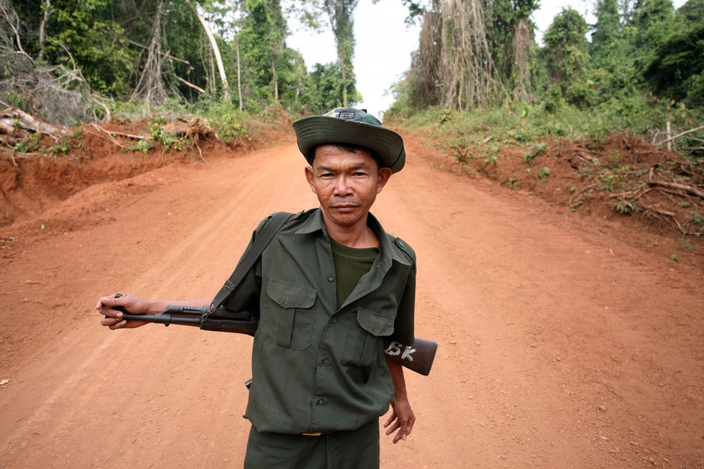A Cambodian soldier secures the road leading through the forest during a raid on some illegal sassafras oil distilleries. Sassafras distilleries that produce the oil from rare Mreah Prew Phnom trees have become a real problem in this area but difficult to stop due to the remoteness of the forest and the high demand and profitablility as the oil can be used as an ingredient for the drug Ecstasy.