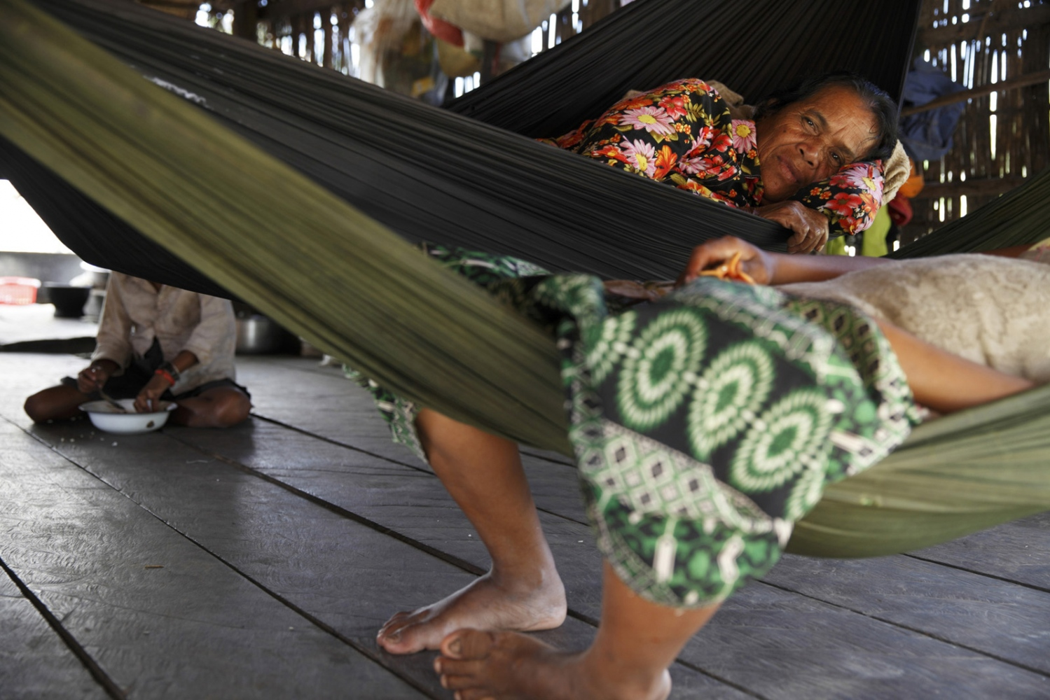 A grandmother and granddaughter rest in hammocks in a house in a village in the Areng Valley of Koh Kong Province.
