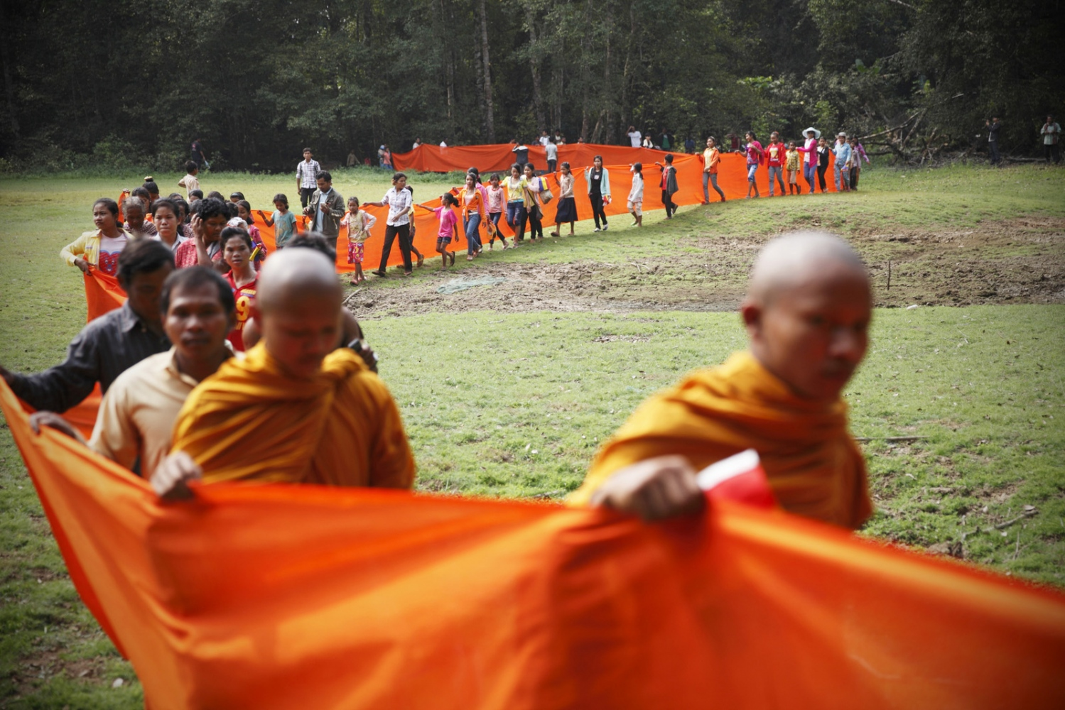 Cambodian Buddhist monks and local people bless large trees by wrapping orange cloth around them and praying. Following uncontrolled forest destruction in the Central Cardamom Protected Forest (CCPF) an eco-warrior monk movement has begun whereby monks and villagers try to protect areas of forest by blessing trees to deter would-be loggers.