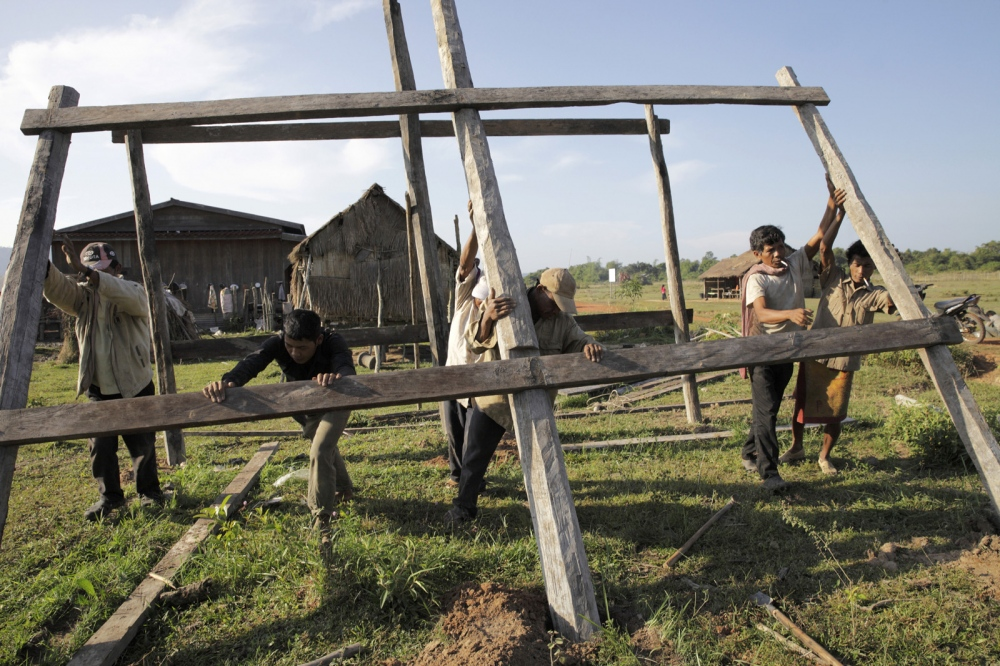 Local men assemble a simple wooden house in Prolay village in the Areng Valley.