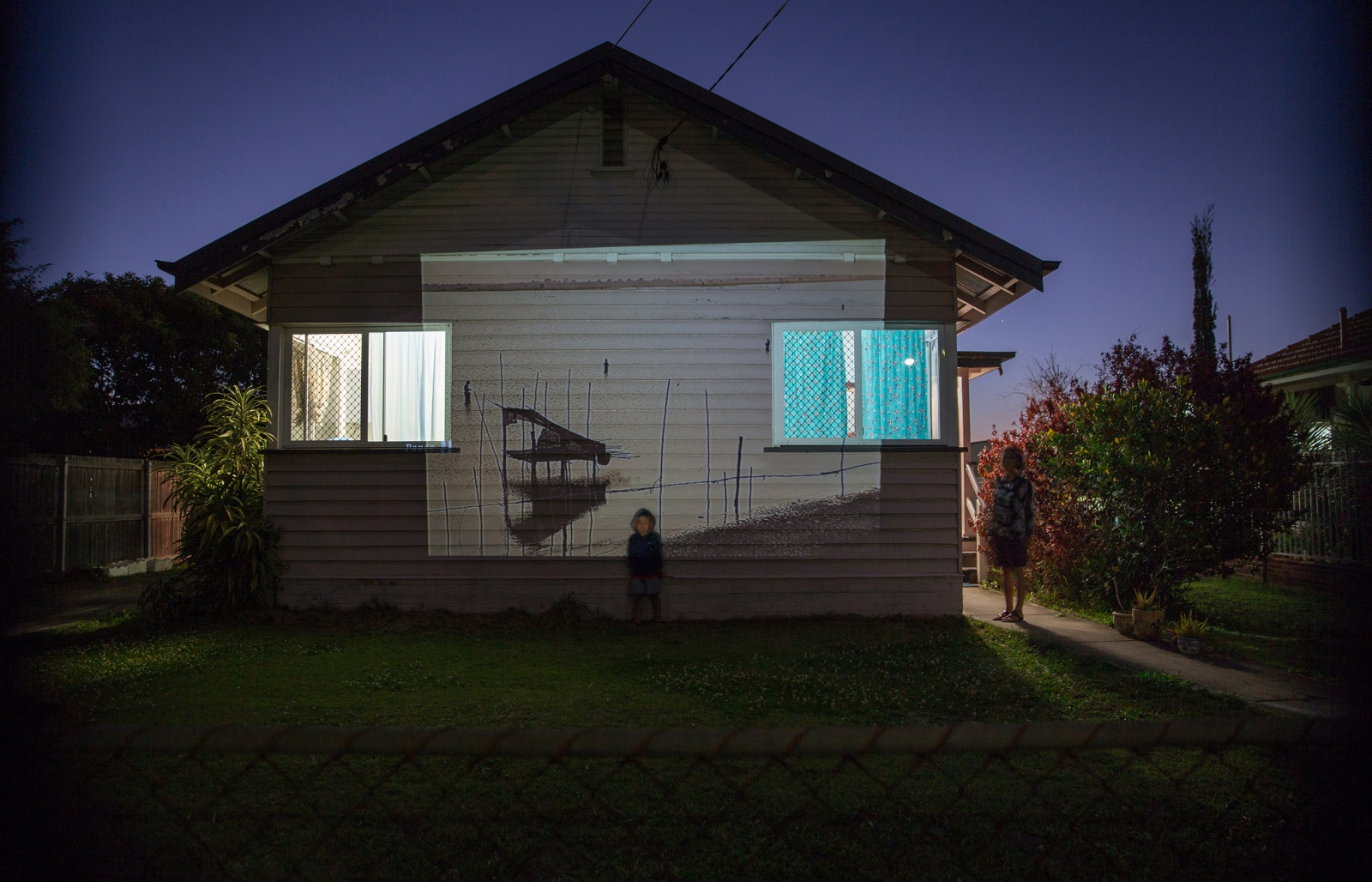 A projection of fishing families in Myanmar. This image has been projected onto the side of a house where a woman and her nephew stand outside their home in Brisbane, Australia. Fish is a staple of the Burmese diet and many who have resettled have told stories of getting caught fishing illegally fishing in newly settled areas as it can be difficult to navigate the local rules and regulations.  QUEENSLAND, AUSTRALIA -  September 2015.